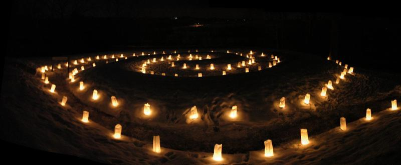 The spiral tail of Serpent Mound lit with luminary candles for the Winter Solstice.