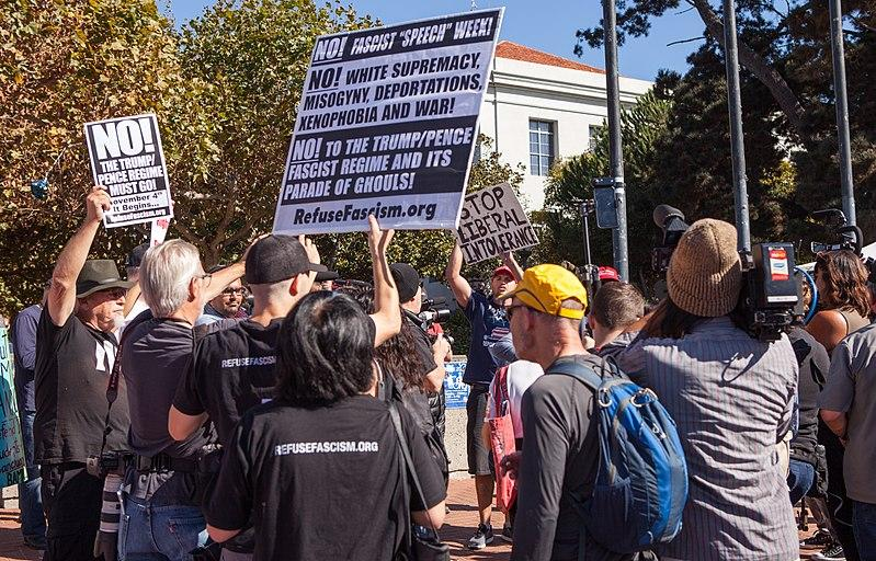 Pro- and anti-Trump demonstrators hold signs on the sidewalk outside Sproul Plaza, UC Berkeley during Speech Week 2017.