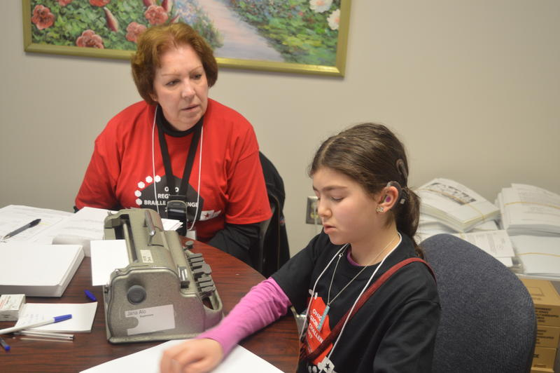 A student sitting at a brailler with a test proctor watching.