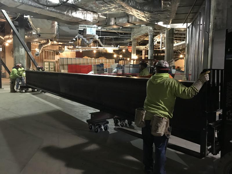 workers move steel beam