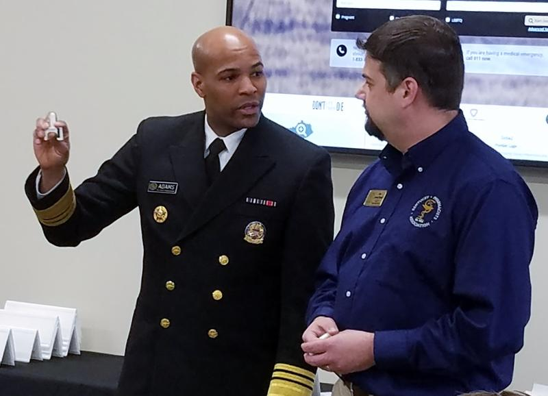 U.S. Surgeon General Dr. Jerome Adams (left) demonstrates how to administer naloxone, a nasal spray.