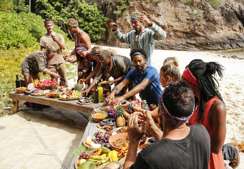 """Survivor"" contestants celebrate ""the merge"" into one camp with a feast on the beach."