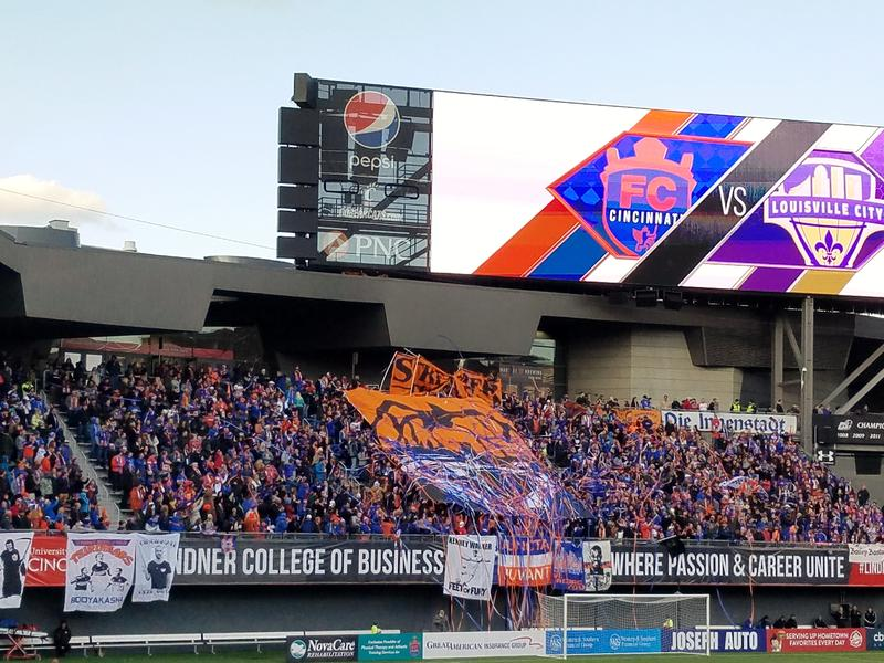 Fans in the FC Cincinnati supporters section throw streamers and unveil a large banner during the team's home opener April 7, 2018