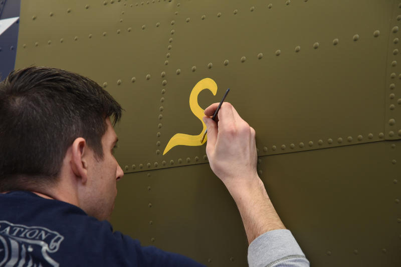 """Museum restoration specialist Casey Simmons paints the letter """"S"""" for """"Sally"""" below the left waist gun position of the Boeing B-17F Memphis Belle as part of the aircraft's restoration."""