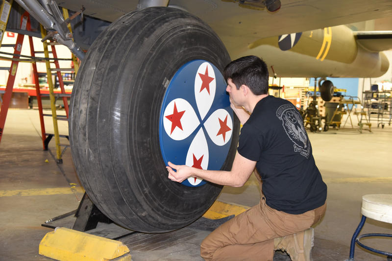 Museum restoration specialist Casey Simmons test-fits the wheel covers on the Boeing B-17F Memphis Belle.
