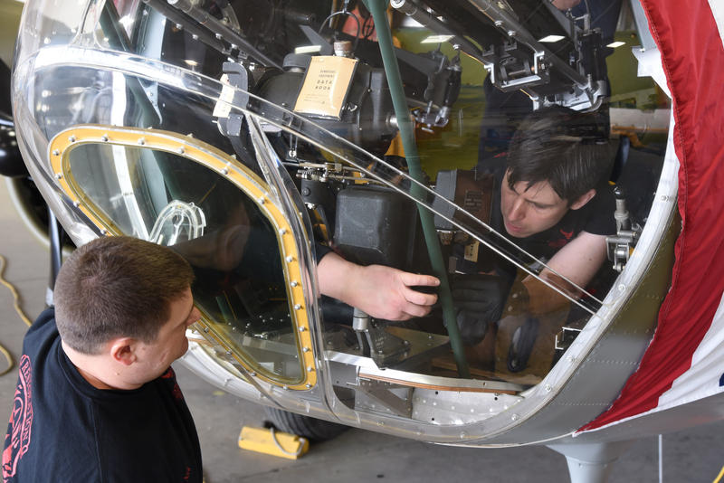 Museum restoration specialists Nick Almeter and Casey Simmons install a bomb sight in the Boeing B-17F Memphis Belle.