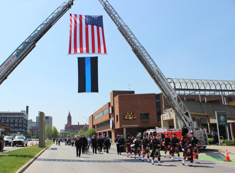 Officers and family members march from the Fire Memorial to the Police Memorial, passing under an aerial flag display provided by the Cincinnati Fire Department.