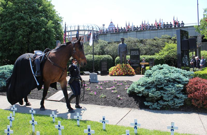 A riderless horse passes in front of the Cincinnati Police Memorial, the black cloth and backwards boots symbolizing the officers who will ride no more.