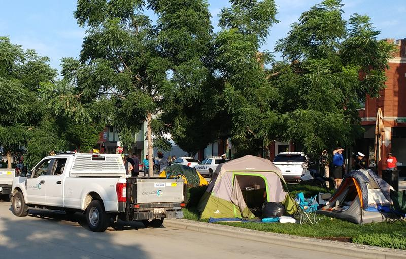 City workers, police and social workers clear out a camp along Central Parkway, Thursday morning.