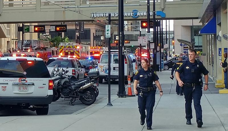 Officer Jennifer Chilton, (left), and an unidentified officer walk away from the Fifth Third Center minutes after the shooting.