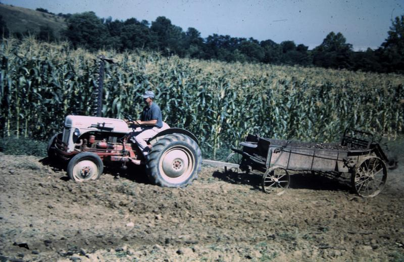 A tractor pulls a manure spreader in 1952.