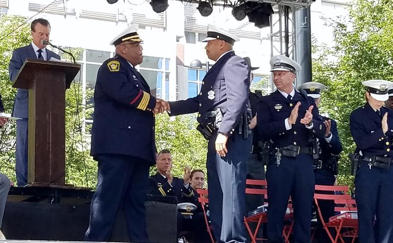 Police Chief Eliot Isaac shakes the hand of Officer Antonio Etter, who left a nearby off-duty detail and engaged the shooter with his own gun. He recieved the Medal of Valor Monday for his actions.