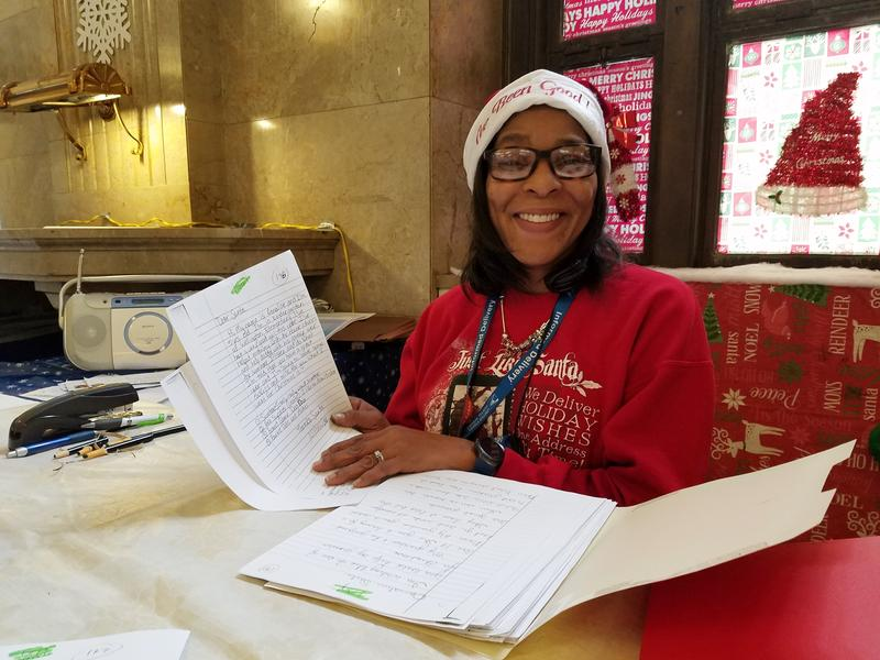 Post Office Quality of Working Life Coordinator Kimberly Davis holds some of the hundreds of letters sent to the post office this year seeking Santa's help for Christmas.