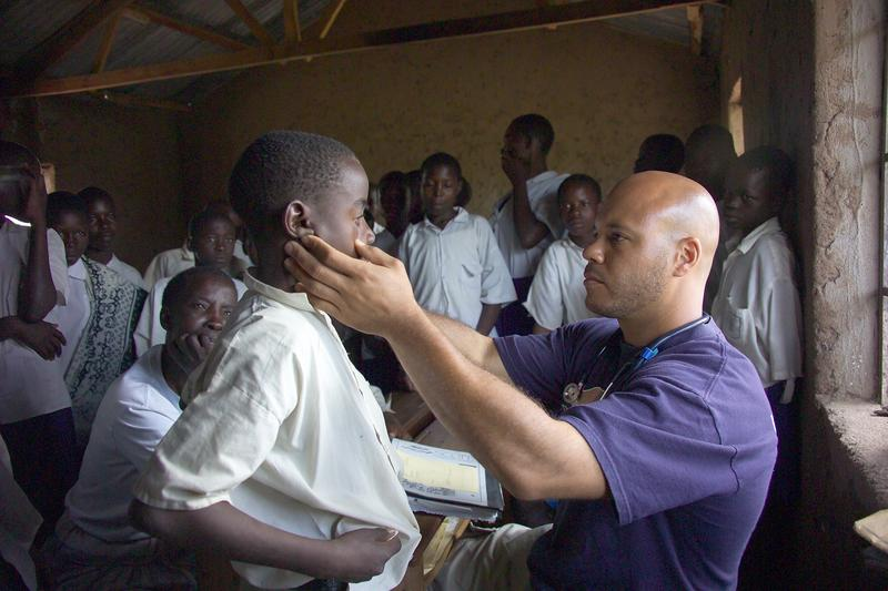 Chris Lewis, MD visits with a patient in Tanzania