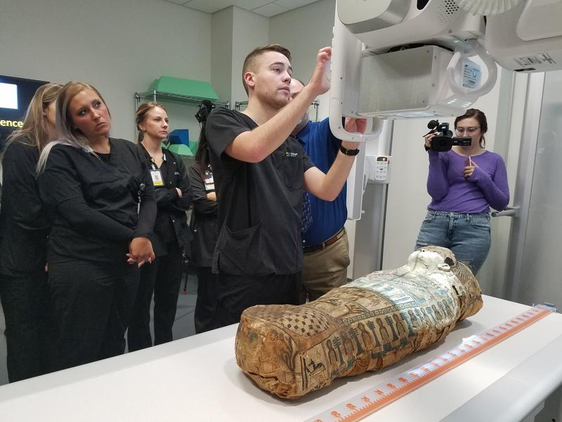 Ryan Chitwood, a third-year radiologic sciences major, positions the X-ray machine above the mummy named Umi as students and faculty look on.