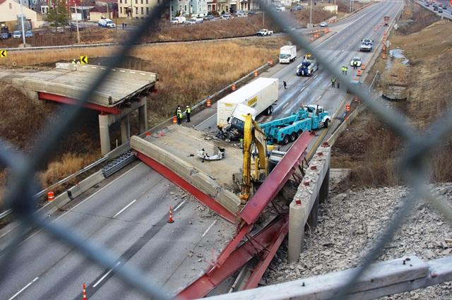 As daylight breaks, crews begin working to pull the semi away from the collapse.