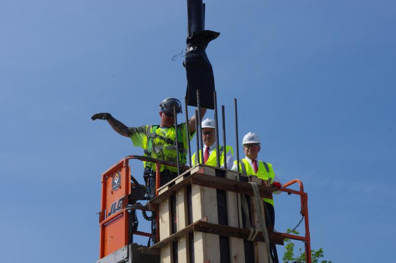 U.S. Representative Brad Wenstrup (center) and Reds owner Bob Castellini pour the second concrete pillar for the newest phase of the Banks.