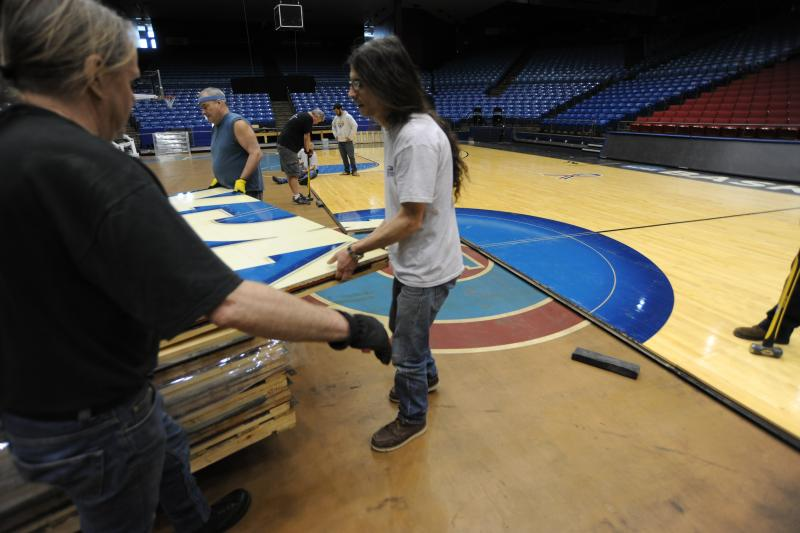 Workers install the First Four floor at UD Arena.
