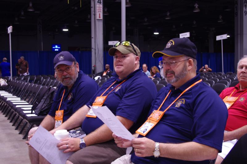 Three members wait for the convention's opening ceremonies to begin.