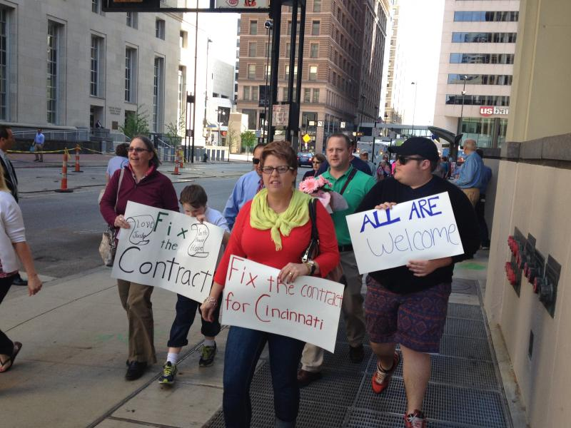 (in front) Molly and Zack Shumate march. Molly is a Catholic elementary school teacher and says she will not sign the new contract. Her son is gay and she feels signing would be taking a big step backward.