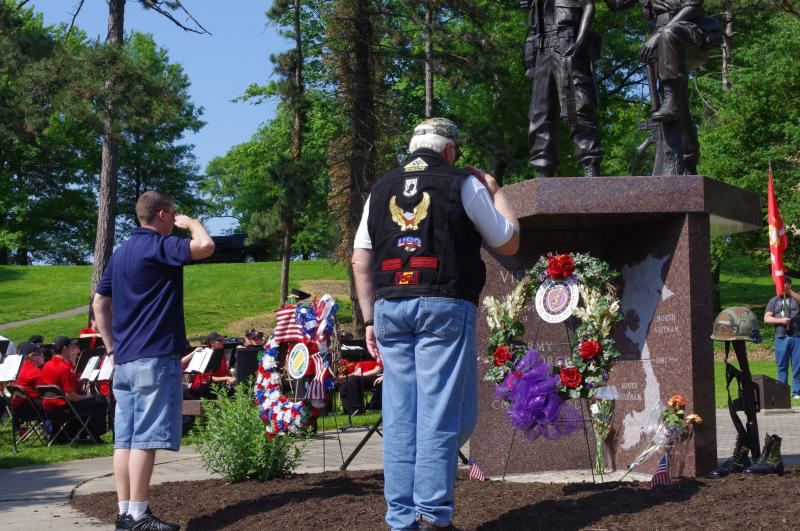 Two former soldiers place wreathes honoring veterans at the base of the Vietnam Memorial.