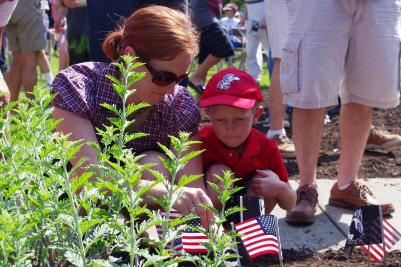 A young boy and his mother place flags at the base of the memorial.