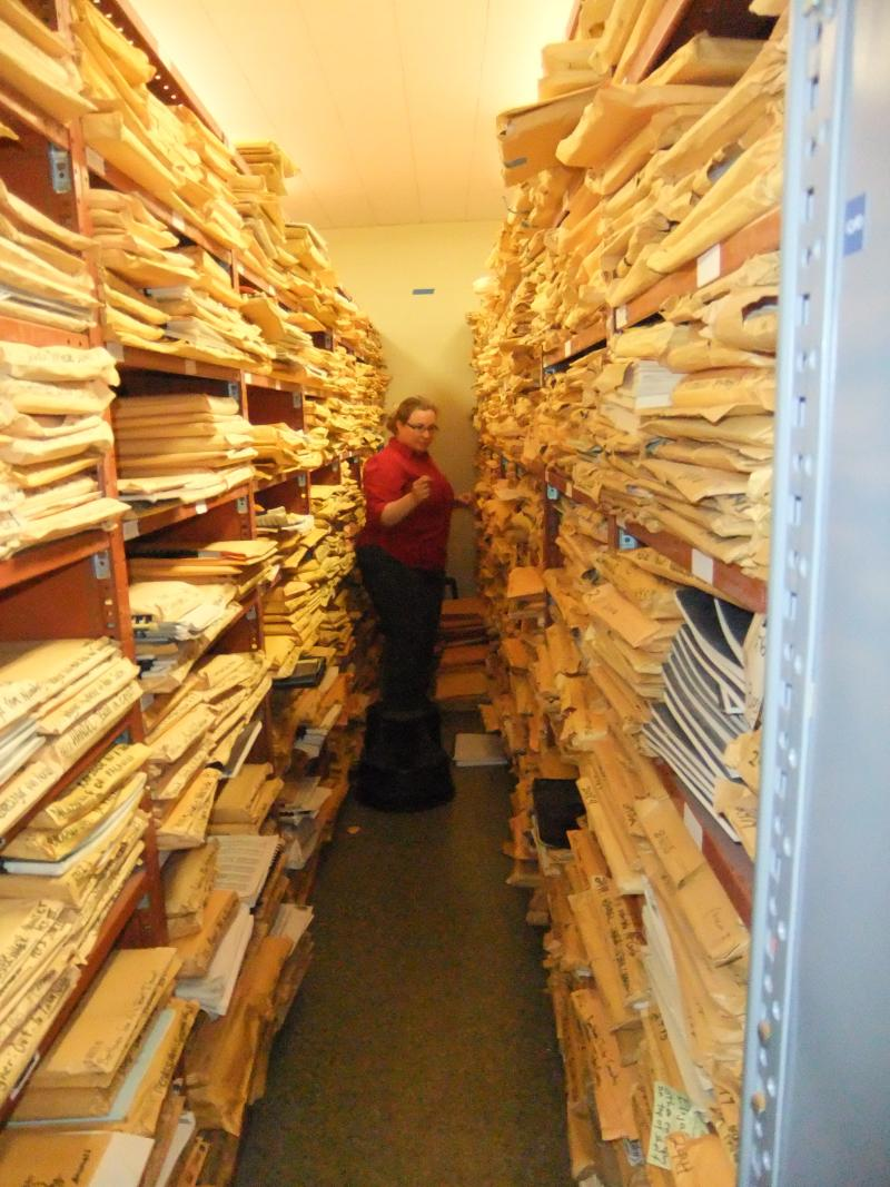 A music librarian stands in one of the narrow, overcrowded library aisles.