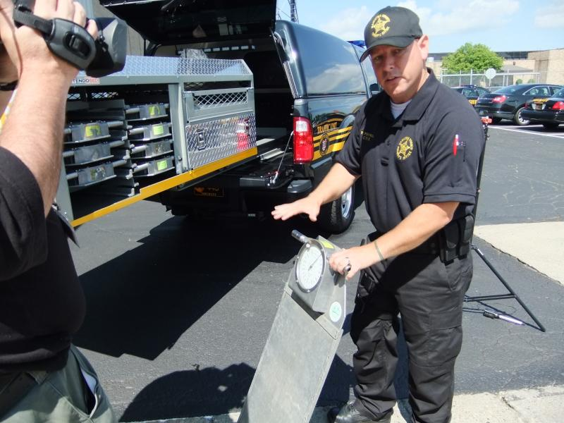 Cpl. Pete Prybal holds a wheel scale he's pulled from the special rack in the back of his customized F-350 patrol truck.