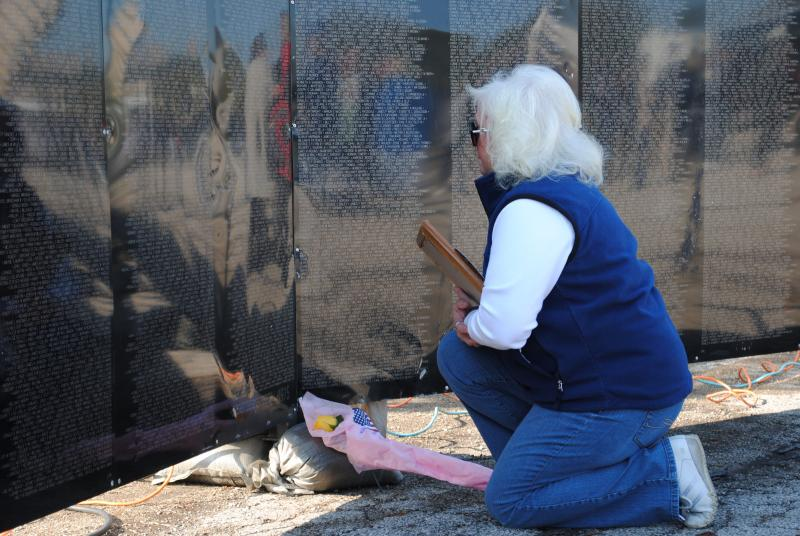 Donna Moore of White Oak lays flowers and an American Flag at the base of the traveling wall.