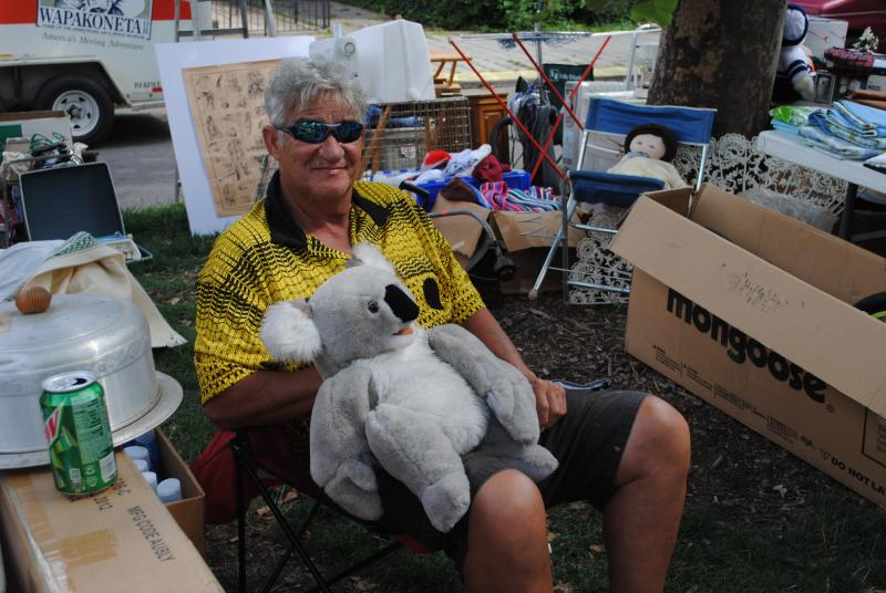 A vendor amuses shoppers with a koala puppet.