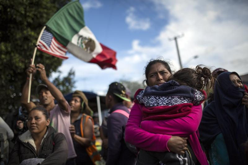 Honduran migrant Leticia Nunes holds her daughter Mailyn as she and others stand in front of a line of Mexican police in riot gear, when they tried to cross the Chaparral border crossing in Tijuana, Mexico, Thursday, Nov. 22, 2018.