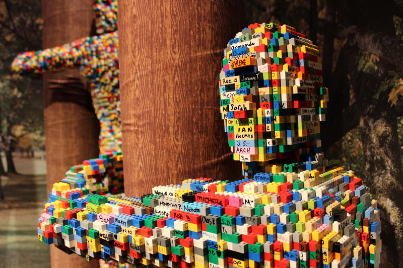 """Visitors can take a """"brickie"""" (selfie) with these treehugging LEGO people. Each brick in this forest is signed by previous visitors."""
