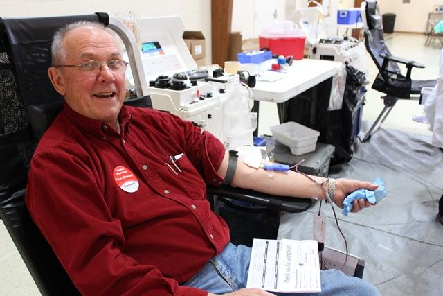 """Jerry Leupen smiles while donating blood. """"It seems to me,"""" he says, """"that {we} who have so much, should be giving blood whether we ever use it or not."""""""