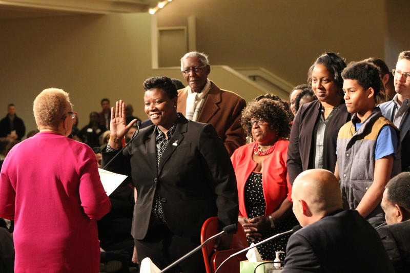 "Newly elected council member Tamaya Dennard takes the oath of office holding a red folding chair, echoing a campaign motto of ""If they don't give you a seat at the table, bring a folding chair."""