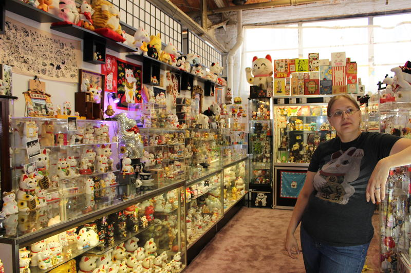 Lucky Cat Museum owner Micha Robertson surrounded by hundreds of beckoning cats.