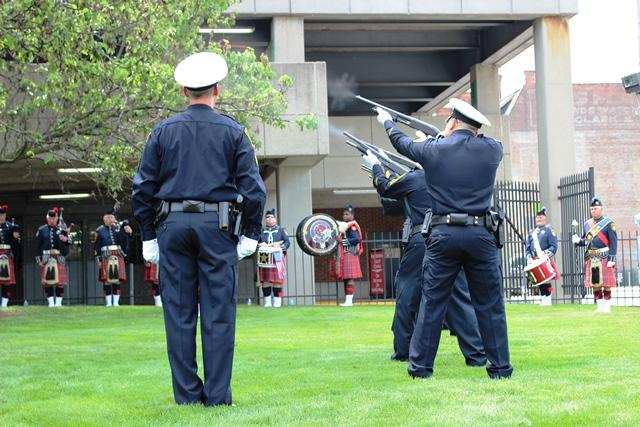 Officers render a 21-gun salute toward the end of the memorial ceremony.