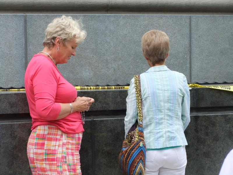 Two women pray the rosary outside the Potter Stewart U.S. Courthouse.
