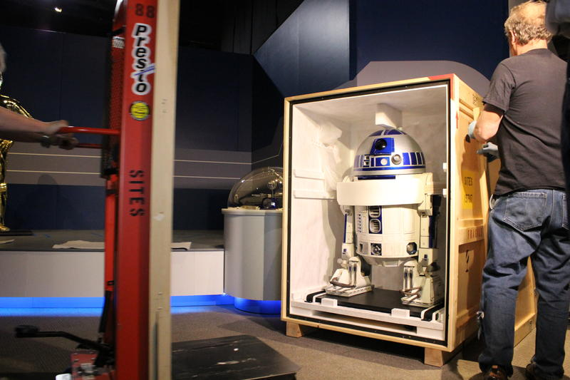 Art handlers removed a crate side to reveal the R2-D2 costume worn by Kenny Baker in the first Star Wars movies.