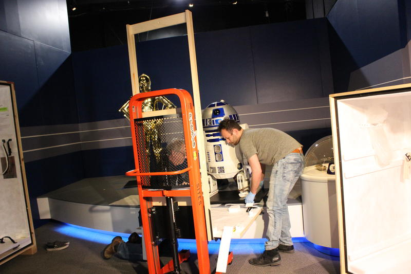 Lifting R2-D2 onto the display platform.