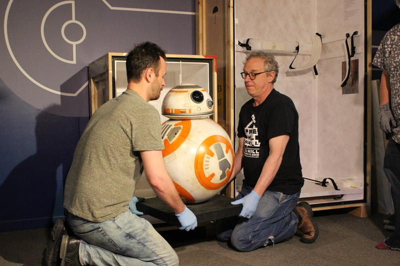 CMC art handlers Robert Burke and Bob Fry carefully lift BB-8 from its crate.