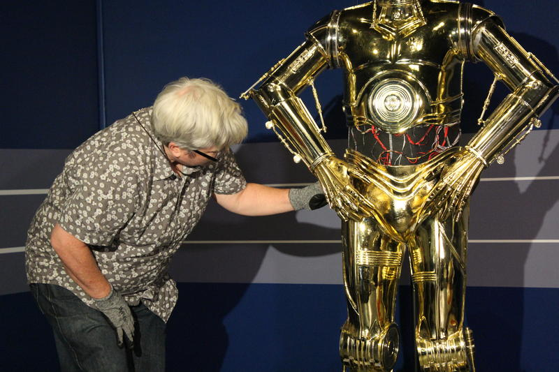 Registrar Ruth Trevarrow checks the C-3PO costume worn by actor Anthony Daniels.
