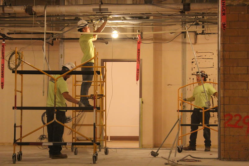 Workers remove some piping in a former classroom space at the Cincinnati Museum Center.