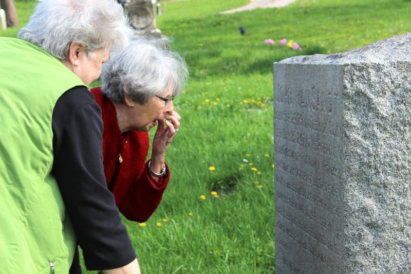 Gretchen Wilson (L) and Kathryn Mereness inspect the headstone of abolitionist John Van Sandt at Wesleyan Cemetery in Northside. Both women are with the Cincinnati Chapter of the Daughters of the American Revolution.
