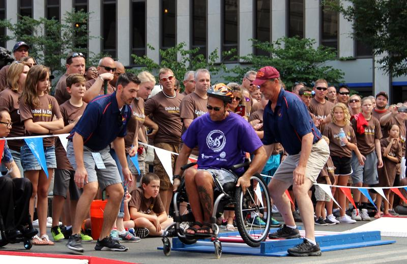 Two spotters follow an athlete through the slalom course to ensure the wheelchair athlete's safety.