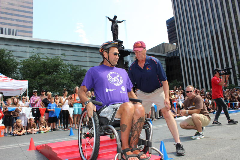 An athlete climbs backward up a stair-stepped obstacle during a demonstration on Fountain Square Monday.
