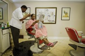 "Last year: Gail Brooks takes in the day's news while Wilbert ""Mr. Chill"" Wilson cuts her hair."
