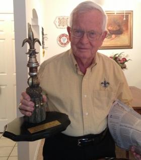 Jerry Romig at his home, holding his Saints Hall of Fame trophy and a copy of the Aug. 16 Baton Rouge Advocate editorial celebrating his career.