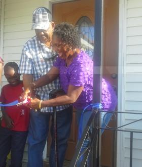 Vanessa Ross cuts the ribbon to her family's renovated Gentilly home.