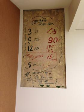 An old sign from the original store preserved and hung in the new Circle Foods, showing passe prices of Chicken in a Box