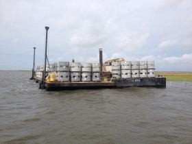 Concrete rings for the oyster restoration project sit on board a barge.